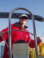Alex at the helm of her first boat, Sea Natural